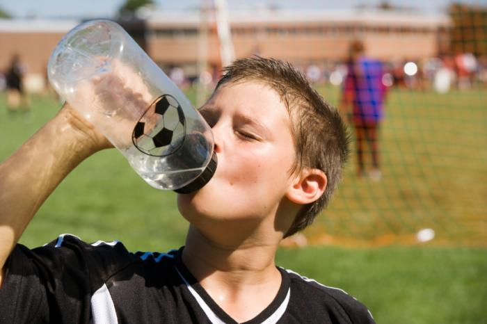 Young footballer drinking water